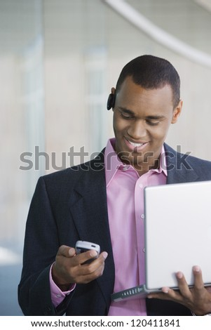 An African American businessman reading text message on mobile phone while holding laptop - stock photo