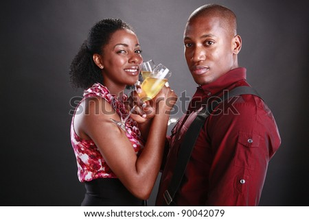 An african american couple cheers with champagne flutes - stock photo