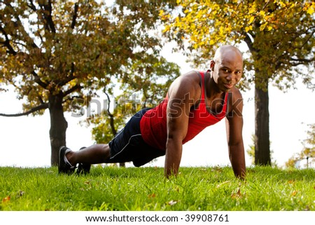 An african american doing exercises in the park - stock photo