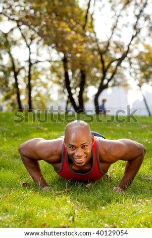 An african american doing push ups in the park - stock photo