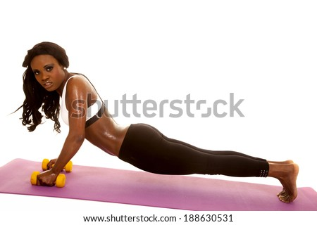 an African American doing push ups on her weighs