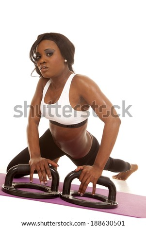 An African American doing some push ups, using push up bars.