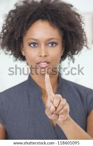 An African American female woman or businesswoman finger raised about to push a button or use a touchscreen touch a screen. The focus is on her finger. - stock photo