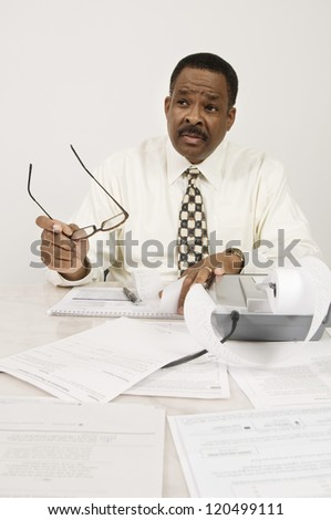 An African American financial adviser communicating with someone while holding glasses in office - stock photo