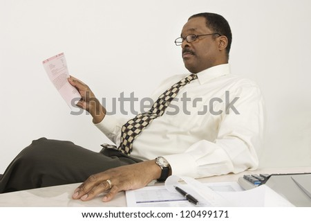 An African American financial adviser with document at desk in office - stock photo