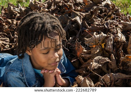 An African American girl praying in a pile of leaves. - stock photo