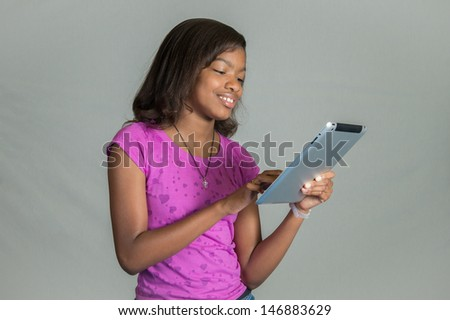 An African American girl using her tablet. - stock photo