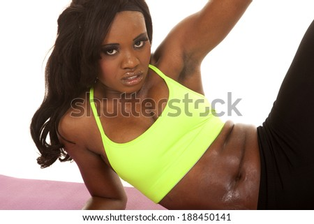 An African American in her fitness clothing and  sweat running off her body. - stock photo