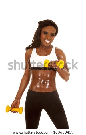 an African American in her fitness clothing holding on to her weights.