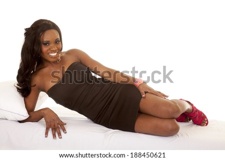 an African American laying on her bed in her black dress.