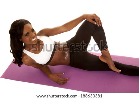 an African American laying on her fitness mat with a smile on her face. - stock photo