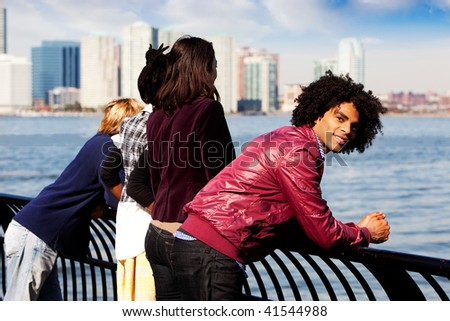 An African American looking at the camera with a group of friends in the background - stock photo
