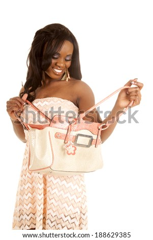 An African American looking down into her bag with a smile. - stock photo
