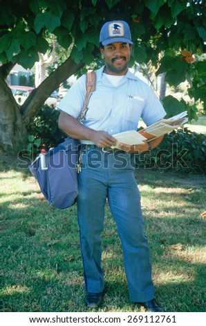 An African-American mail carrier on his route, Santa Monica, CA - stock photo