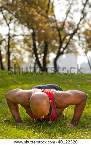 An african american male doing push ups in a park - stock photo