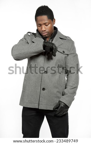An African American male model wearing a gray jacket and white t-shirt underneath with black pants and black leather gloves in a studio setting on a white background. - stock photo