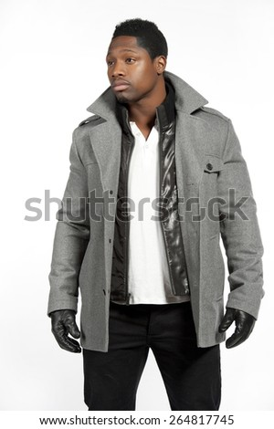 An African American male model wearing a gray jacket and white t-shirt underneath with black pants and black leather gloves in a studio setting on a white background while looking to the left. - stock photo