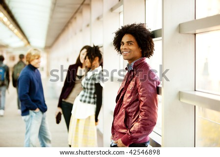 An African American male with friends talking in the background - stock photo