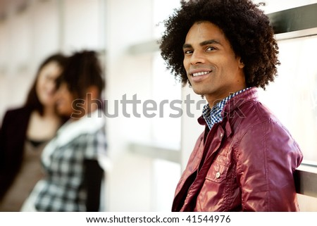An African American male with two women talking in the background - stock photo