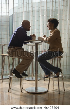 An African-American man and woman enjoy each other's company over a cup of coffee.  They are seated at a small cafe table on stools. Vertical shot. - stock photo