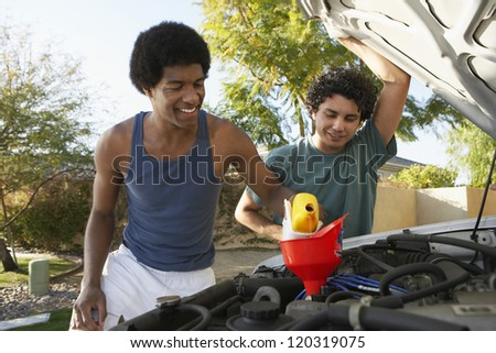 An African American man oiling the engine of the car with friend standing besides - stock photo