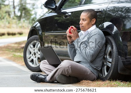 an African American man on the road next to his car with a laptop drinking coffee - stock photo