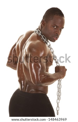 An African American man shirtless holding a chain. - stock photo