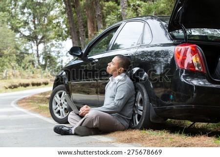 an African American man sitting beside the car on the road with laptop looking at the horizon - stock photo