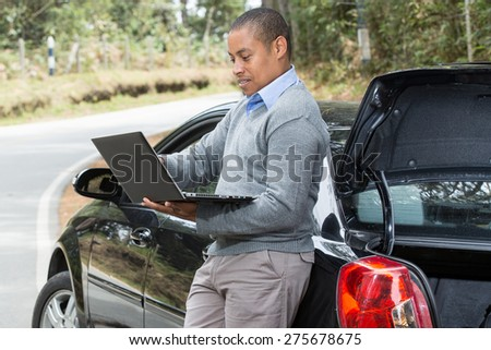 an African American man standing beside the car on the road looking at the screen of your laptop - stock photo