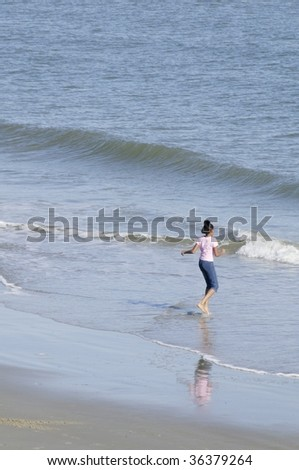 An African-American preteen girl dancing at the ocean. - stock photo