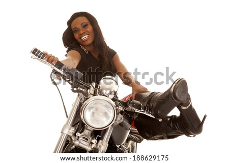 An African American relaxing on her motorcycle with a smile on her face.