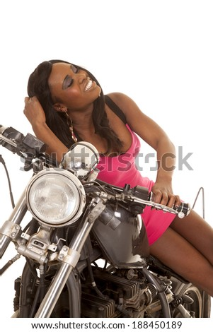 an African American sitting on her motorcycle wearing her pink dress. - stock photo