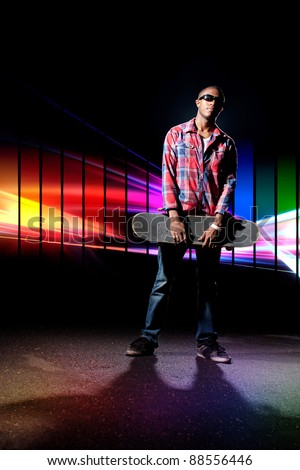 An African American skateboarder  holding his skateboard deck under dramatic lighting with a creative rainbow color schemed glowing spectrum in the background. - stock photo