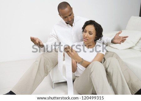 An African American upset couple with expense receipt at home - stock photo