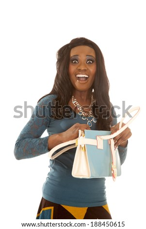 An African American with a scared expression on her face holding on to her bag. - stock photo