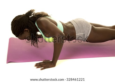 An African American woman doing a push up.