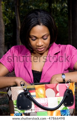 An African American woman going trough her purse - stock photo