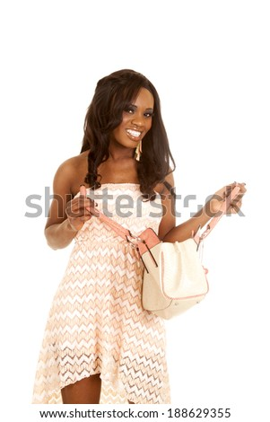 An African American woman in her peach dress, looking down into her bag.