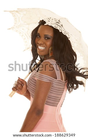 An African American woman in her pink dress, holding on to an umbrella with a smile. - stock photo