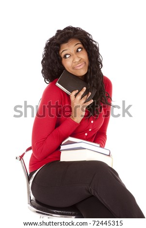 An African American woman is holding a book by her face. - stock photo