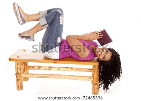 An African American woman is laying on a bench with a book. - stock photo