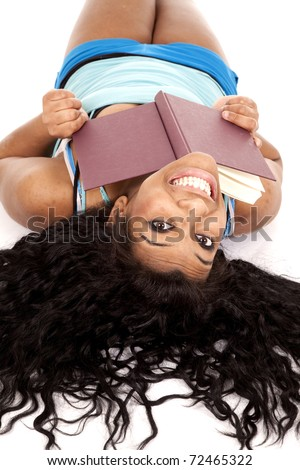 An African American woman is laying upside down with a book and a smile. - stock photo