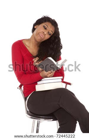 An African American woman is reading a sad book. - stock photo