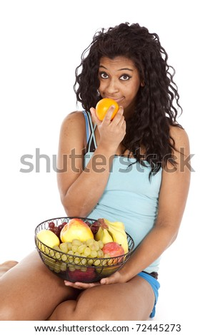 An African American woman is ready to taste some fruit. - stock photo