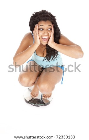 An African American woman is sitting on the scales with her hands on her face. - stock photo