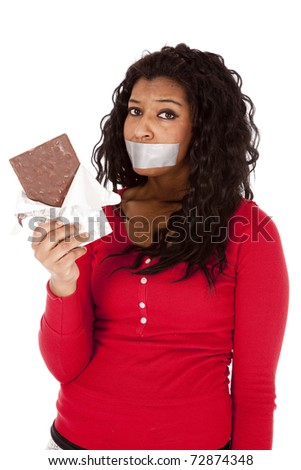 An African American woman is wanting to eat chocolate but has tape over her mouth. - stock photo