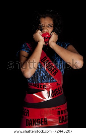 An African American woman is wrapped in danger tape and is mad. - stock photo