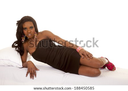 an African American woman laying on her bed in her black dress. - stock photo