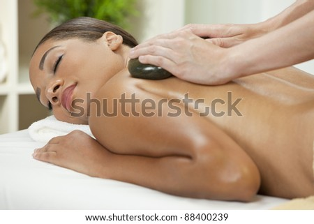An African American  woman relaxing at a health spa while having a hot stone treatment or massage - stock photo