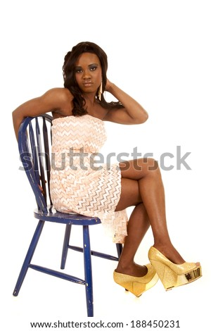 an African American woman sitting in her blue chair in her fancy dress and fun shoes. - stock photo